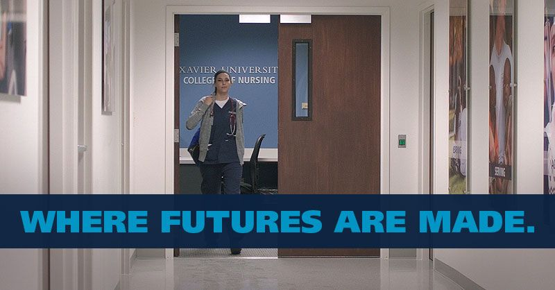 Xavier nursing student walking through hallway - Where Futures Are Made.